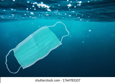 Surgical mask thrown into the sea. Image about ocean pollution and the consequences of overuse of surgical masks during coronavirus pandemic.