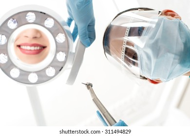 Surgical masked female dentist adjusting dental mirror