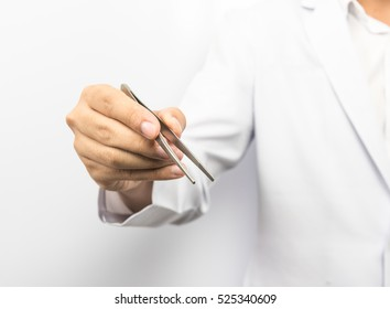 Surgical and Medical theme: a doctor's hand hold forcep on white background in studio.