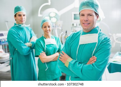 Surgical team smiling with arms crossed in an operating theatre