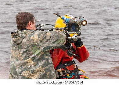 Surgut, Russia, 06.10.2019: Assistant helps the diver to put on the helmet. Deep-sea work.