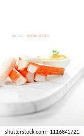 Surimi ocean sticks with out of focus seafood cocktail sauce with dill herb garnish. Generous accommodation for copy space.