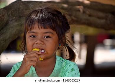 Surin Island, Thailand  - March 06, 2018: Moken child is eating a yellow mango