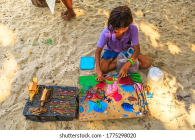 Surin Islands, Phang Nga, Thailand - January 3, 2016: top view of a Sea Gypsies little girl selling necklaces and bracelets in Moken fisherman village of Ko Surin Marine Park.
