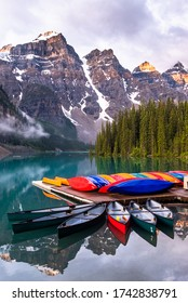 Surise Illuminates The World Fameous Torquoise Waters of Moraine Lake and Colorful Canoes. 				Banff / Lake Louise National Park, Canadian Rockies, Alberta
