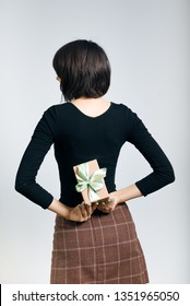 Surprise! beautiful business woman hiding a gift behind her back, isolated on gray background