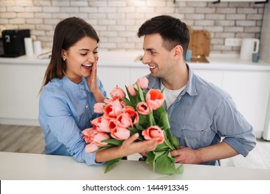 Surprise! Beautiful romantic couple at home. Young man is presenting flowers to his beloved. Feel of happiness. Celebrating Woman`s day, birthday.