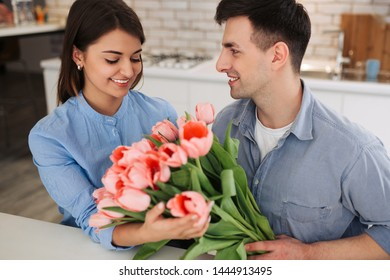 Surprise! Beautiful romantic couple at home. Young man is presenting flowers to his beloved. Feel of happiness.