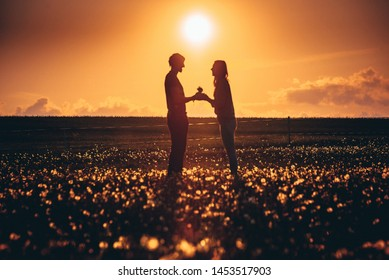Surprise! Beautiful romantic couple on dandelions field. Young man is presenting flowers to his beloved. Feel of happiness.