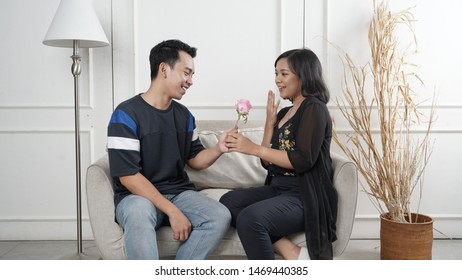Surprise! Beautiful romantic south east asia couple at home. Young man is presenting flowers to his beloved. Feel of happiness.