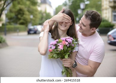 Surprise: Boyfriend with bouquet of flowers holding his  hands over his girlfriend�´s eyes