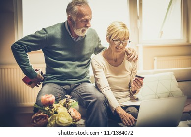 Surprise causes a smile. Senior couple at home with credit card and laptop. Senior man holding gift for his wife.