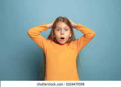 The surprise, delight, happiness, joy, victory, success and luck. The surprised teen girl on a blue studio background. Facial expressions and people emotions concept. Trendy colors