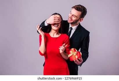 Surprise! Excited and happy couple in love are hugging, kissing and celebrating the St Valentines day. Celebration, holidays and gifts concepts. St Valentines dat. Lovers day