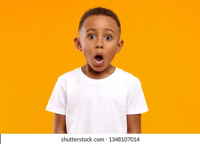 Surprise, excitement and fascination concept. Funny bug eyed African little boy opening his mouth widely, shocked with astonishing unexpected news, having amazed look, showing full disbelief - Shutterstock ID 1348107014