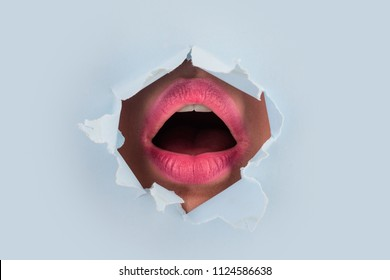 Surprise. Female mouth in colored with pink lipstick is through hole in paper. Seductive female mouth is open in torn paper. Women sexy mouth inside. Scream and the right to vote. Feminism and voting
