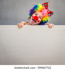 Surprise! Funny kid clown. Child holding banner blank. 1 April Fool's day concept