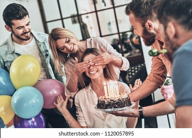 Surprise for her. Group of happy people celebrating birthday among friends and smiling while having a party