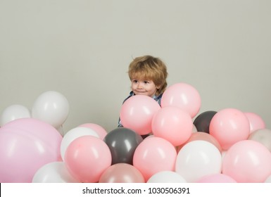 Surprise. Hide and seek for children surrounded with balloons. Little kid hides in colourful balloons. Child with cute smile hides in pink, grey and white balloons. Decorations for children's Birthday