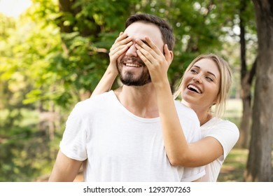 Surprise moment. Portrait of man closing eyes women with hands while she is smiling
