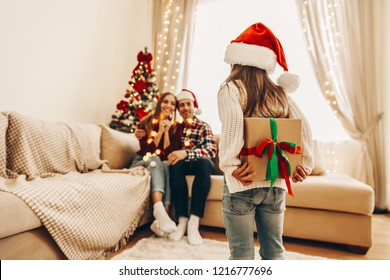 Surprise for parents.Christmas. Family. Presents. Little girl is holding a gift box for her parents behind her back. At home near the Christmas tree