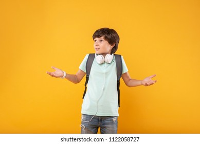Surprise. Perplexed smart schoolboy wearing a schoolbag and having his headphones around the neck