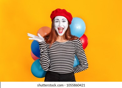 Surprise! Portrait of cute mime woman holding many colorful balloon
