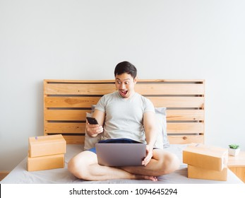 Surprise and shock face of Asian man success on making big sale of his online store. Concept of freelance startup and online business home office.