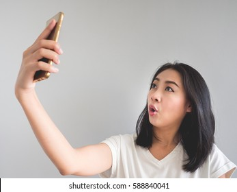 Surprise and shock face of Asian woman look at the smartphone in her hand.