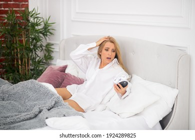 Surprise. Shocked long-haired woman looking surprised at watch in bed clutching head with hand