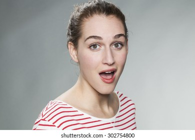 surprise and success concept - beautiful 20s woman wearing a striped sweater expressing surprise and happiness on her face