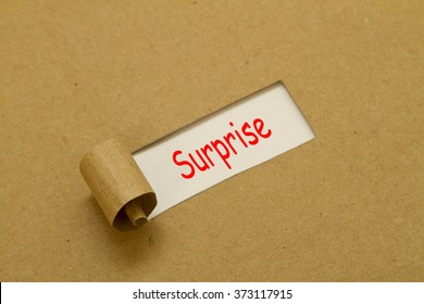 Surprise word written under brown torn paper