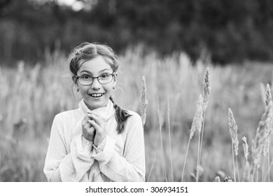 Surprised adorable teenage girl in glasses at autumn field.