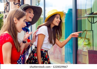 Surprised adult women females girls friends in colorful dresses and hats in shopping mall or cloth store looking for new fashion clothes in shop's window. Shop sales, discount, black friday concept