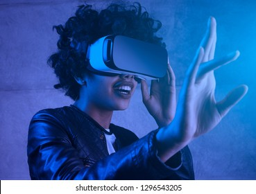 Surprised african american young woman touching experiencing VR helmet. Portrait toned in blue filter