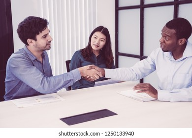Surprised African businessman supporting idea of colleague and shaking his hand. Amazed handsome investor approving new startup project at meeting. International partnership concept