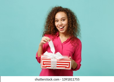 Surprised african girl in pink clothes hold red striped present box with gift ribbon isolated on blue turquoise wall background. International Women's Day birthday holiday concept. Mock up copy space