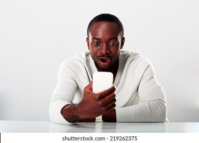 Surprised african man sitting on the table and looking at smartphone