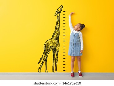 Surprised African-American girl measuring height near color wall with drawn giraffe