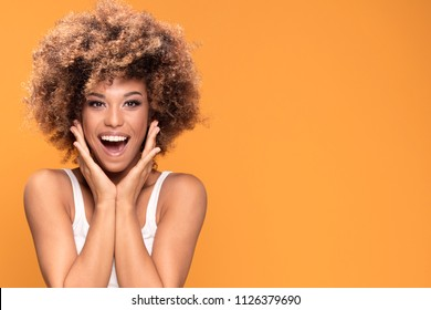 Surprised amazed beautiful afro woman with wide open mouth looking at camera, smiling. Girl posing on yellow background.