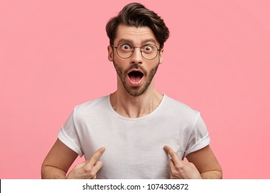 Surprised amazed fashionable guy with stubble, wears casual white t shirt, indicates at blank copy space for your text, stares at camera surprisingly. People, clothing and advertising concept