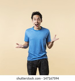 Surprised and amazed looking Asian man standing against cream background.
