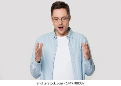 Surprised amazed young European man in eyeglasses with open mouth looking down and demonstrating big size wide copy space for advertisement, isolated on grey studio background portrait.