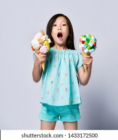 Surprised asian baby girl kid holds two sweet big ice-cream in waffles cones with tasty marshmallow jelly beans can not believe her luck exclaims Oh My God on pink background