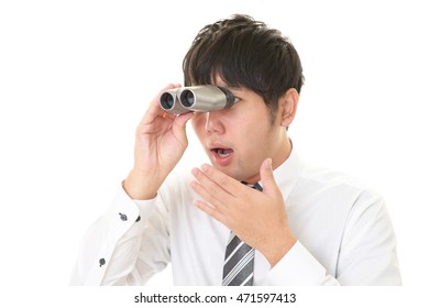 Surprised Asian businessman with a binoculars