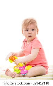Surprised baby girl playing with  colorful flower toy