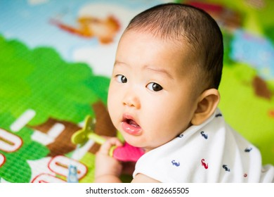 The surprised baby lying on mat in bed room