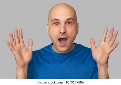 Surprised bald guy. Shocked man looking at camera. Isolated on grey