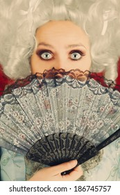 Surprised  Baroque Woman Portrait with Wig and Fan - Baroque style portrait of a surprised beautiful woman behind a hand fan