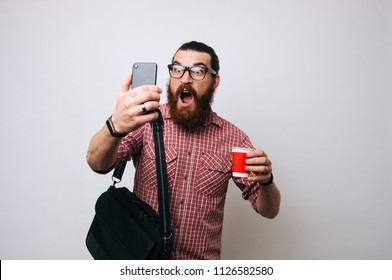 Surprised bearded man looking at his smartphone going to work. Winning money online by the phone. Man with work bag holding a red paper cup with tea or coffee, cappucino or latte in red plaid shirt.
